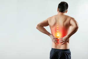 Rear view, the man holds his hands behind his back, pain in the back, pain in the spine, highlighted in red.