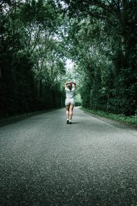 woman-in-white-t-shirt-walking-on-concrete-road-2792083