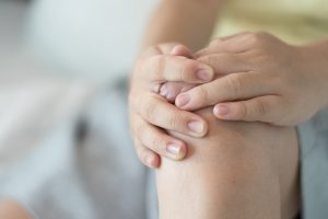 Knee injury pain concept. Hands on leg as hurt with painful from accident.